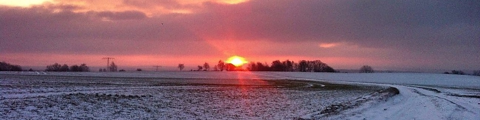 Sunrise on a snowy road and field